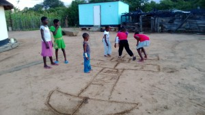 On the wet African soil, kids love to draw and play games.